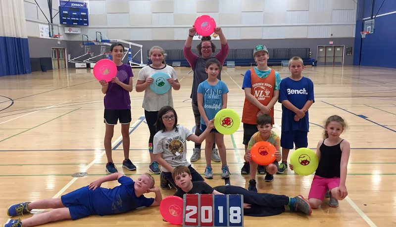 Elementary-aged participants in our summer elementary camp are pictured with discs.