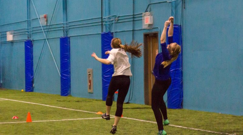 Two female-matching players jump for the disc in the St. John's Women's Ultimate Recreational League (SWURL).