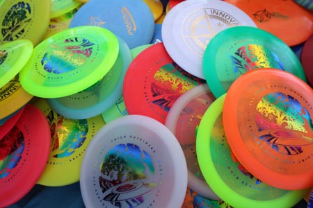 A photo of colourful ultimate frisbee discs gathered in a pile.