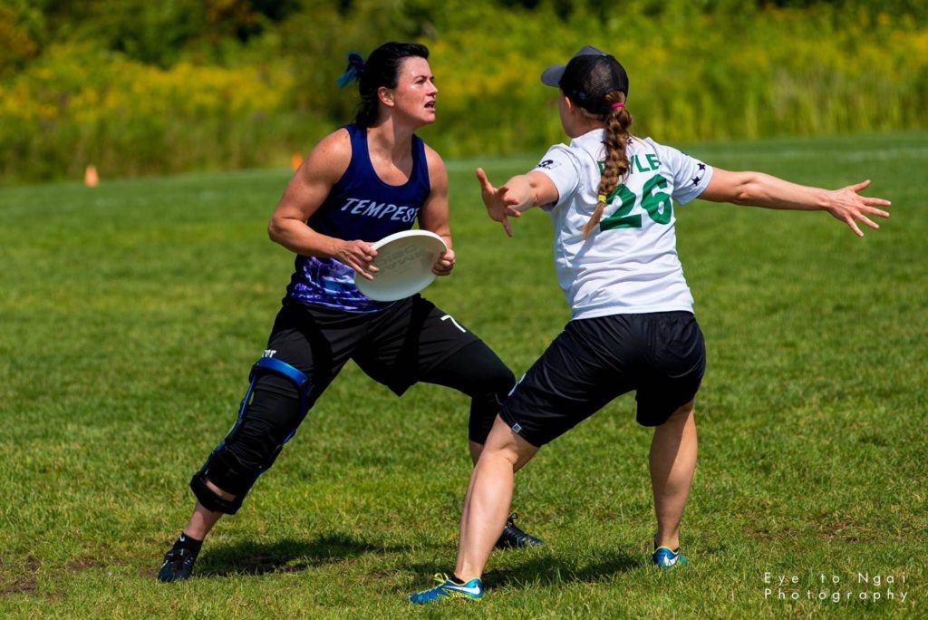 Jessica Wade is pictured holding the disc and wearing a Tempest jersey while an opponent guards her.