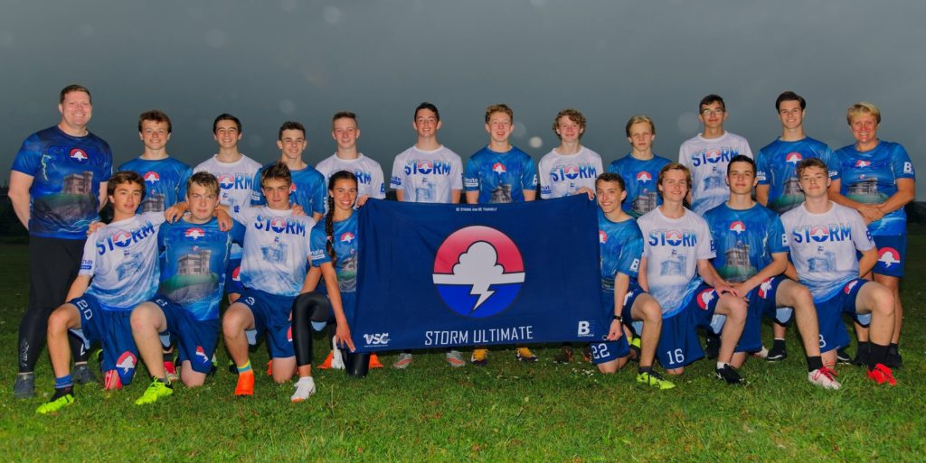 A team picture of the 2019 open Storm team with two members holding a flag with the Storm logo.