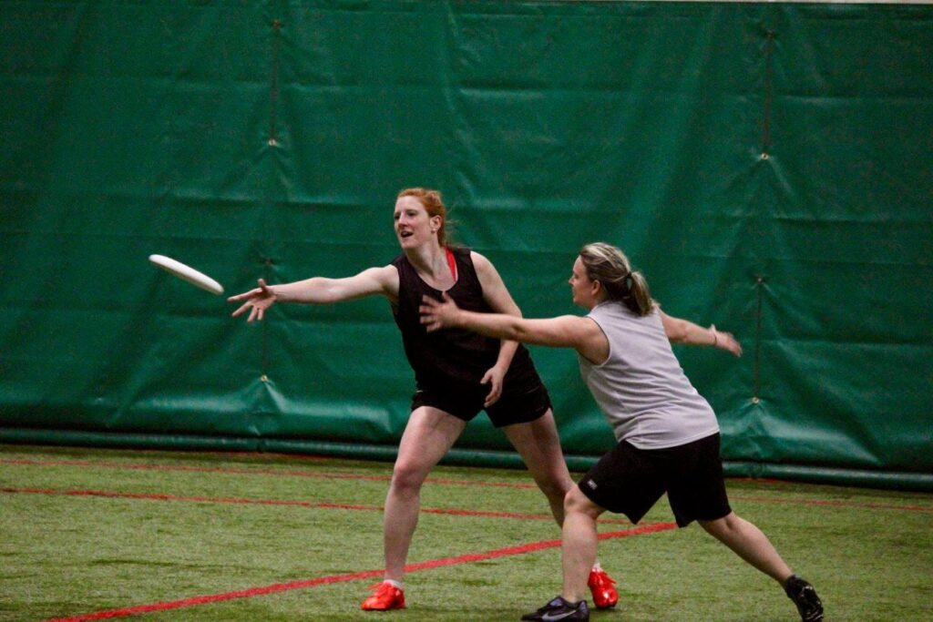 Two female-matching players face off in a photo from the St. John's Women's Ultimate Recreational League (SWURL).